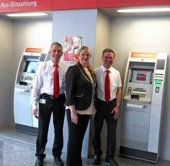 Eugen Bakes, Manuela Dinkel und Norbert Kleemann von der Sparkasse Fürth zwischen den beiden 5-Kassetter-Recyclern im SB-Bereich der HauptstelleWincor-Nixdorf