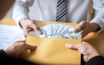 Dishonest cheating in business illegal money, Businessman giving bribe money in envelope to business people to give success the deal contract of investment, Bribery and corruption concept.