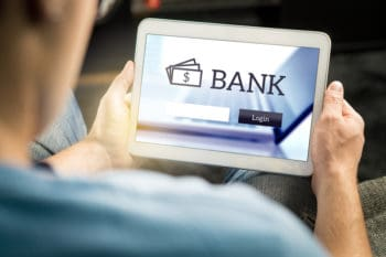 Man using mobile bank application with tablet and smart device at home. Login page to personal account. Online internet banking. Imaginary financial institution website or app.