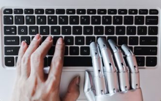Robot hands and fingers point to laptop button advisor chatbot robotic artificial intelligence concept