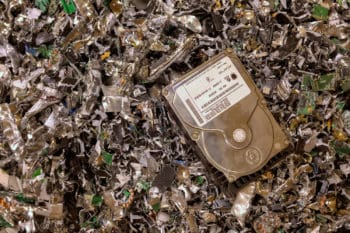 A hard drive resting on a pile of shredded hard drives